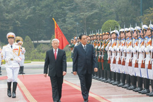 President Choummaly Sayasone (right) inspects a guard of honor on his arrival in Vietnam.